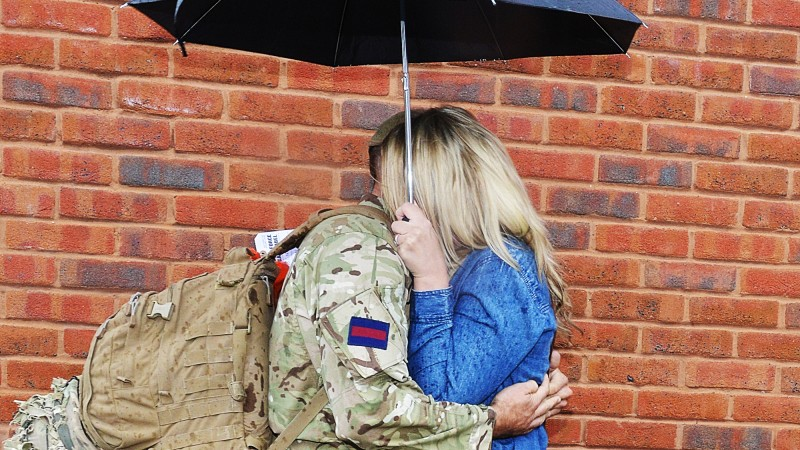 Forces family love couple hug brickwork umbrella Credit: Defence Imagery