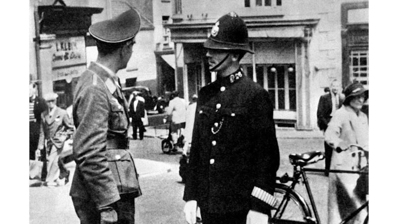 A Luftwaffe officer speaking with a British policeman in St. Helier, the capital of the island of Jersey, during the German occupation of the Channel Islands 010741 cropped for cover CREDIT PA