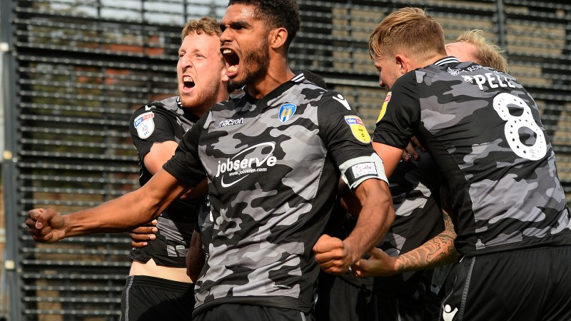 Colchester United players celebrate a last-gasp equaliser against Mansfield Town in their camo away kit (Picture: Colchester United).