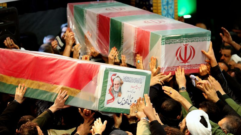 Iran mourners carrying caskets of Qasem Soleimani (L) and Iraqi paramilitary chief Abu Mahdi al-Muhandis (R)