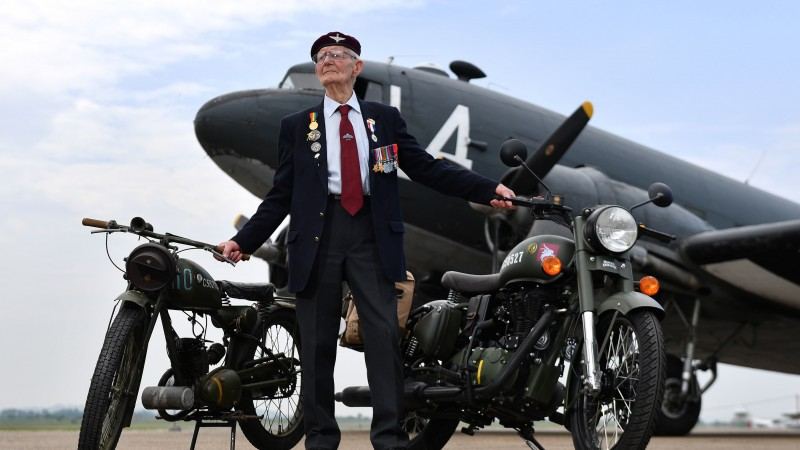 Fred Glover, 92, who served in the parachute regiment during World War II, stands on the airstrip at Imperial War Museum Duxford with a limited edition Royal Enfield 'Classic 500cc Pegasus' motorbike