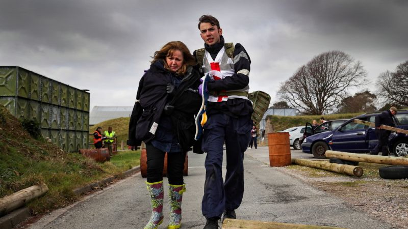 HMS Kent sailor with civilian at disaster relief exercise