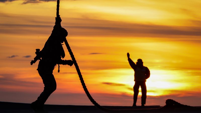 Silhouetted anonymous Royal Marines embarked on board HMS Queen Elizabeth doing fast rope training