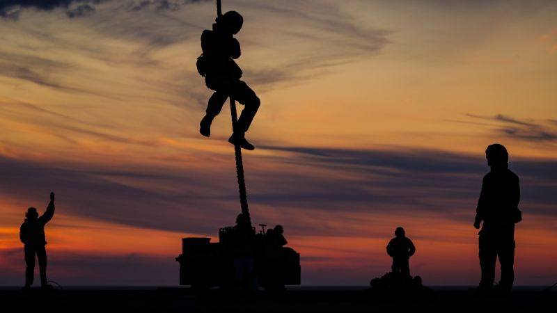 Silhouetted anonymous Royal Marines from Lima Company 42 Commando doing fast rope training
