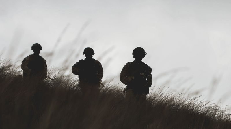 Silhouetted anonymous Royal Marines on a joint personnel recovery exercise on Dartmoor