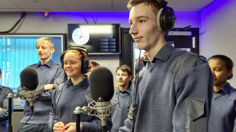 Uniformed RAF Air Cadets in headphones on the microphone in the Forces Radio BFBS studios