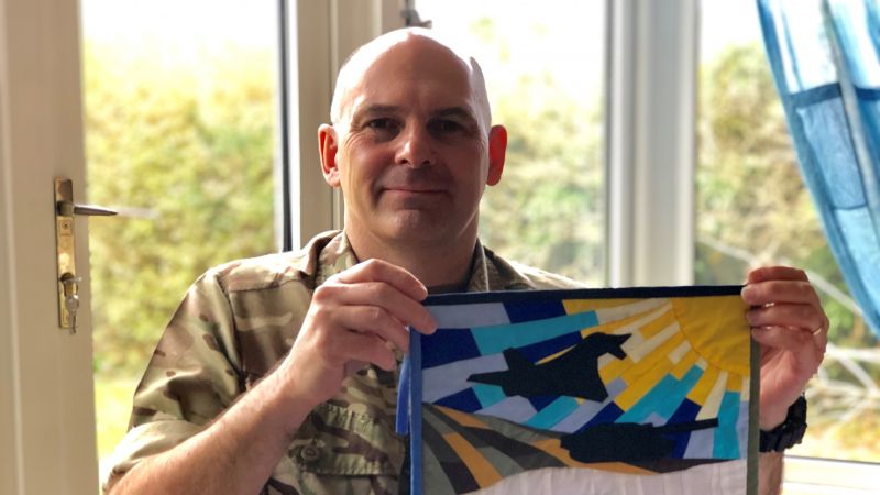"""Sewing Soldier"" Neil Stace, holding up a flag he has sewn"