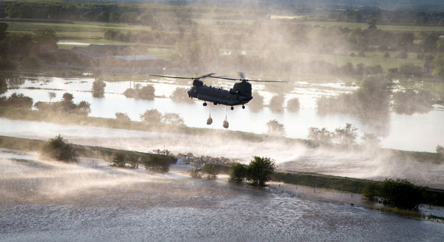 Chinook helicopter lowers bag of aggregates into the breach of a riverbank in an effort to stop the river Steeping causing further flooding to the local area CREDIT RAF