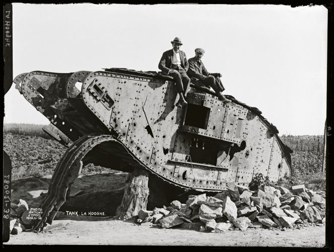 Two Belgian farmers sit on the wreck of the World War 1 British tank