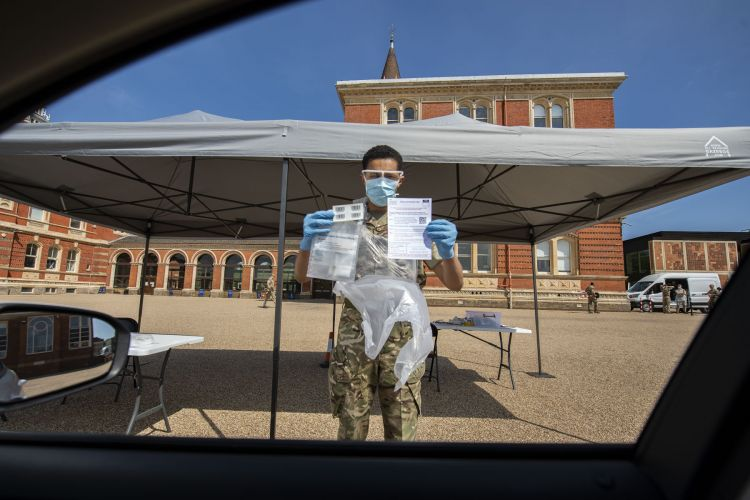 Troops from The Grenadier Guards held up cards to explain how to complete COVID19 Coroanvirus testing in Dulwich