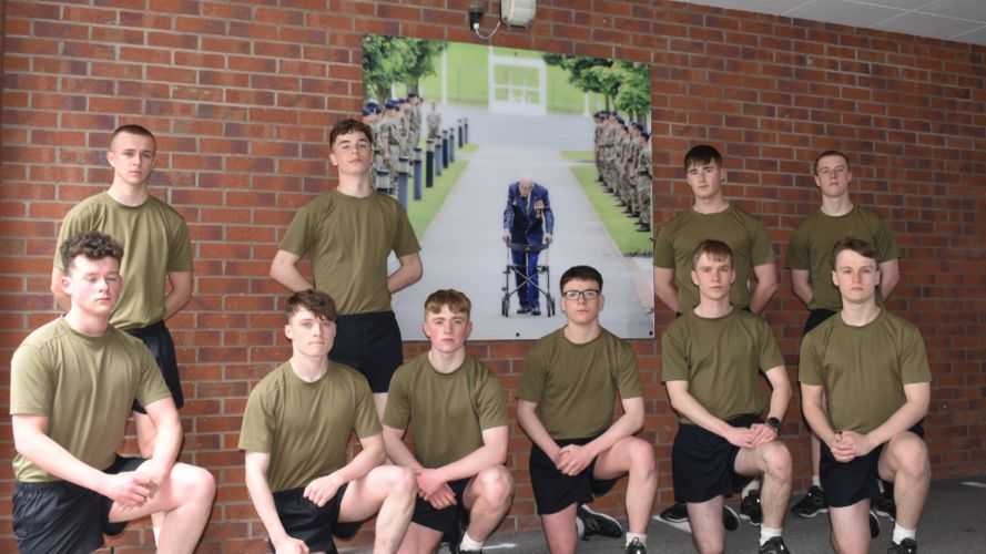 UK Armed Forces personnel pose in front of a picture of Captain Tom Moore amid efforts to take on the Captain Tom 100 challenge (Picture: MOD).