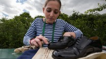 Private Richards polishes her shoes before dressing smartly