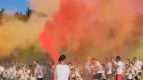 Runners starting off the colour run at Depsey Barracks, running through a haze of orange, pink and yellow paint