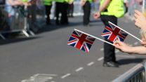 Anonymous hands holding Union flags British flags at Armed Forces Day