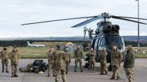 A Puma helicopter and its support team gather for a brief after landing at Kinloss Barracks (Picture: MOD).