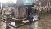 A young girl pays her respects on Armistice Day at 3 Rifles memorial garden, Redford Barracks Edinburgh.