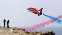 Red Seven of the Red Arrows screams past photographers waiting on a cliff edge during a practice display over RAF Akrotiri in Cyprus.