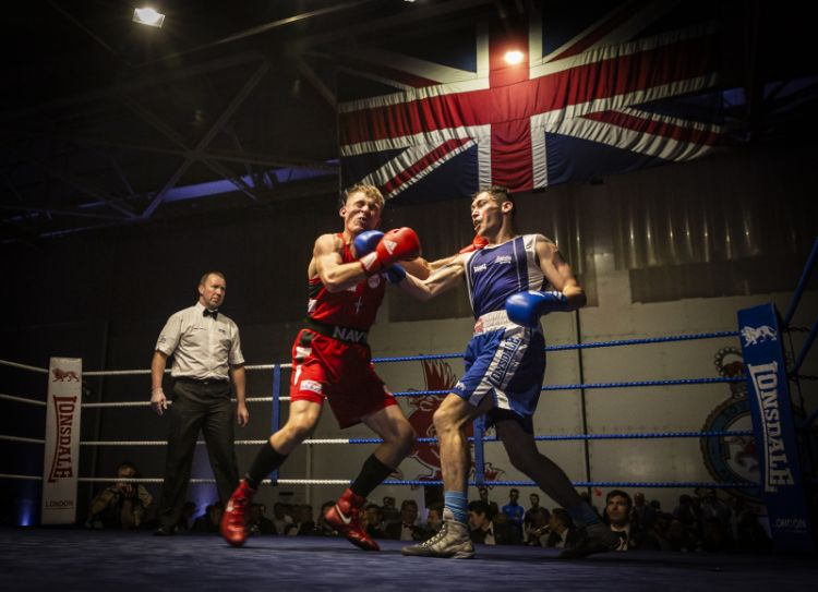 SAC (Senior aircraftman) Arran Devine (right), delivers a powerful uppercut on his Royal Marine opponent (left).