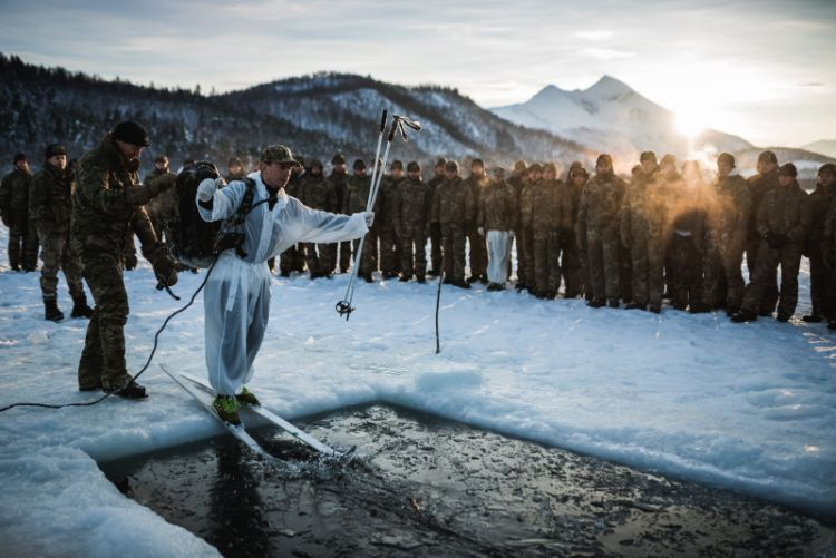 A Royal Marine from 40 Commando, about to slide into icy water, during an ice breaking drill in Norway