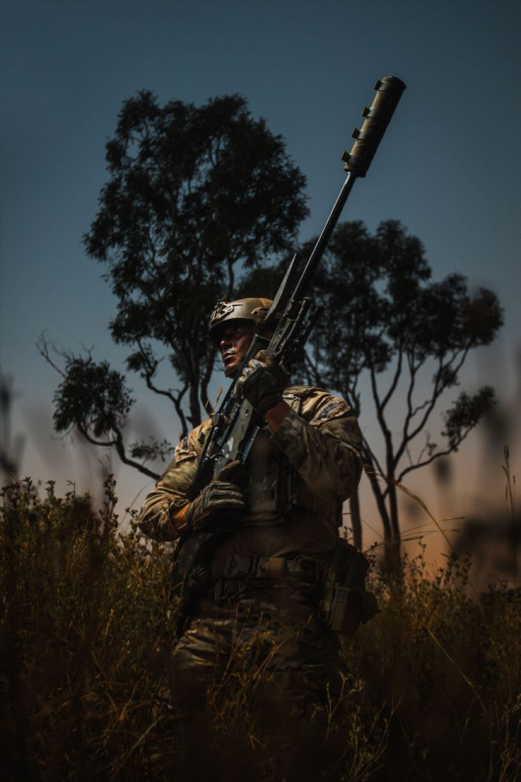 A Royal Marines Commando, patrols through the Australian bush with a .338 sniper rifle at dusk on exercise Talisman Sabre 19 in Queensland, Australia.