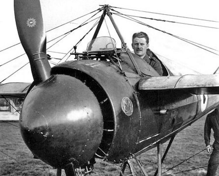 A pilot sitting in a French Morane-Saulnier N, with a deflector placed in front of the machine gun