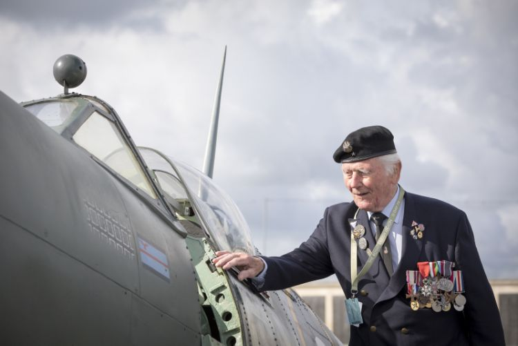 a veteran looking at a replica RAF Spitfire at the D-Day 75 National Commemorative Event in Portsmouth.