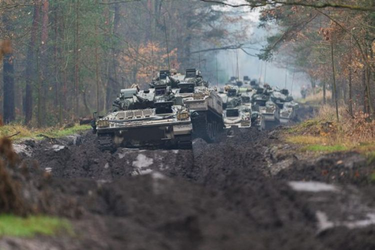 A column of Warrior armoured fighting vehicles moving along an autumnal forest track in Poland during Exercise Black Eagle 190319 CREDIT MOD.jpg