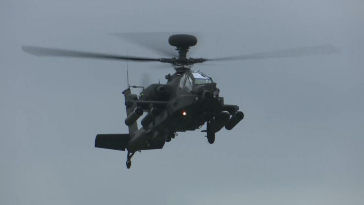 Apache helicopter flying into the training ground.