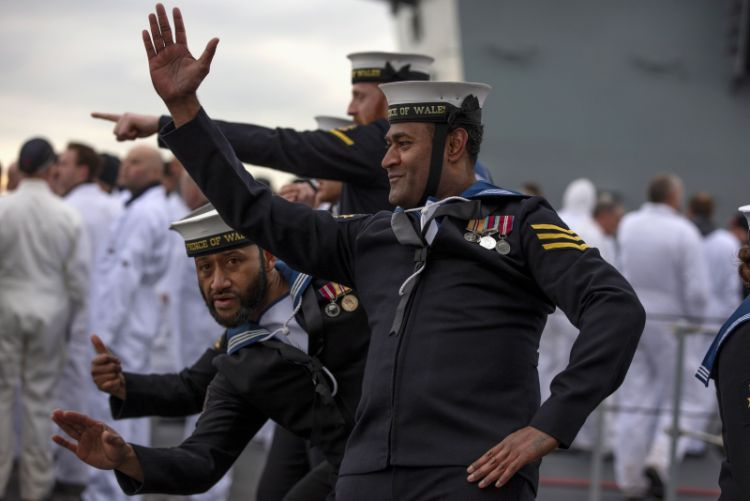 Sailors from HMS Prince of Wales, wave to the crowds as she comes into Portsmouth Harbour.