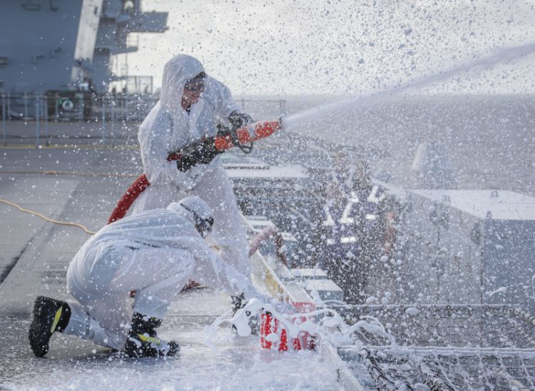 HMS Queen Elizabeth Flight deck crews testing out part of her foam firefighting capability, the tests were to establish that the foam mixture was correct and was achieved by collecting the foam from the high pressure stream into buckets.