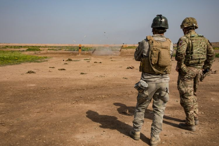 British soldier observes explosion with Iraqi soldier at Camp Taji