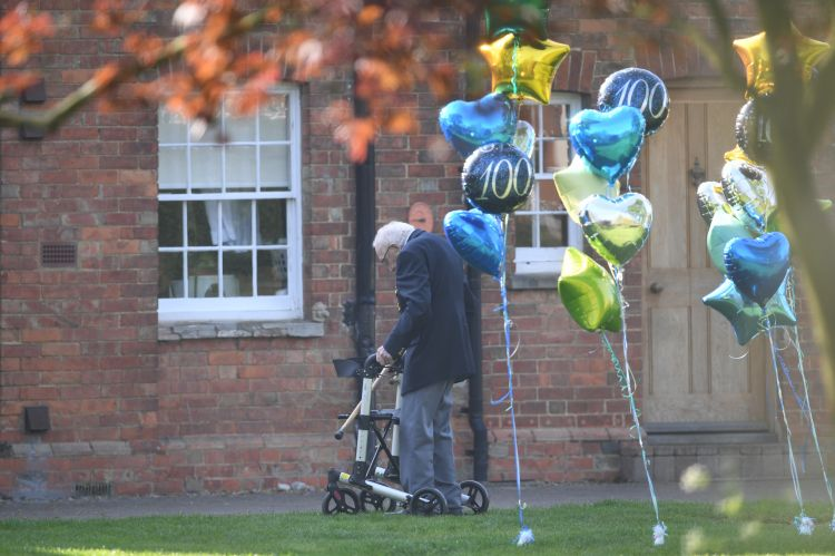 Captain Tom Moore with balloons outside his Bedfordshire home