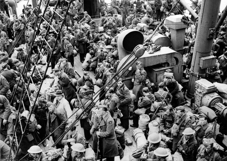 RAF airmen crowd the deck of a steam Boat during Operation ARIEL