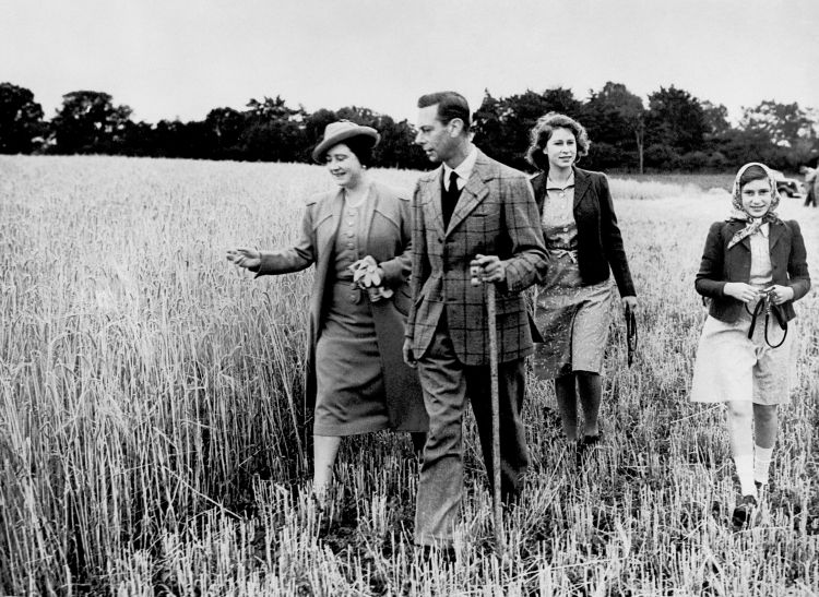 During the Second World War, King George VI and Queen Elizabeth walk in a field with Princess Elizabeth and Princess Margaret (right) 300942 CREDIT PA