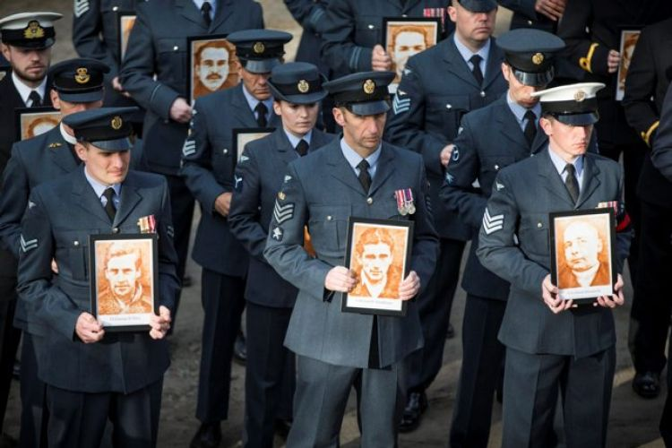 Each RAF Officer and Airman held a single photo of each of the 50 Great Escape members that were killed upon capture (Picture: MOD).