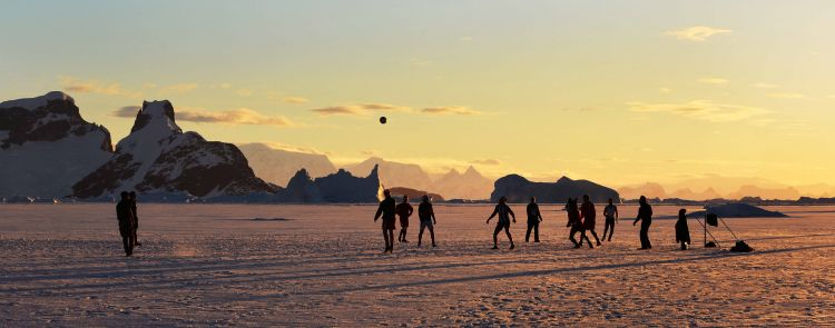 Members of HMS Protectors Ships Company play football on the ice as the sun sets in Antarctica Credit Defence Imagery Royal Navy LA(Phot) Vicki Benwell