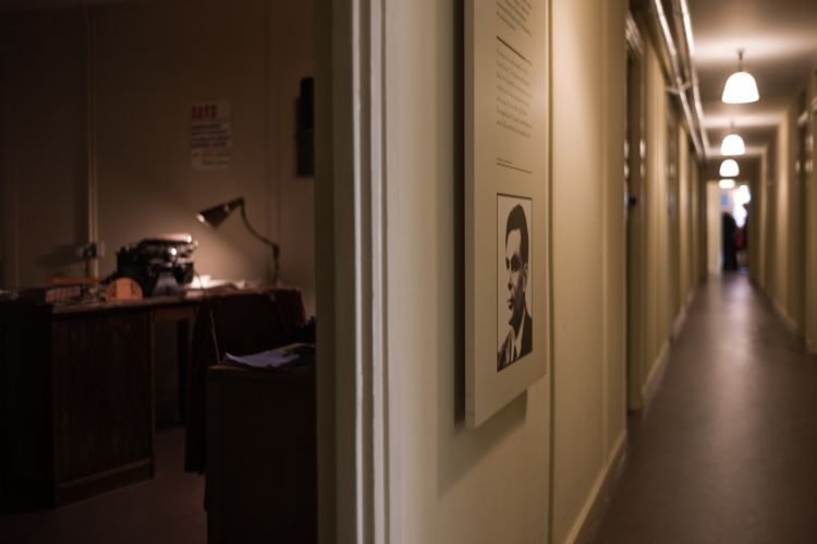 A side-view of Alan Turing's office in Hut 8, Bletchley Park. A desk lamp lights up an old typewriter on a desk in the corner; Turing's picture is on the corridor wall.