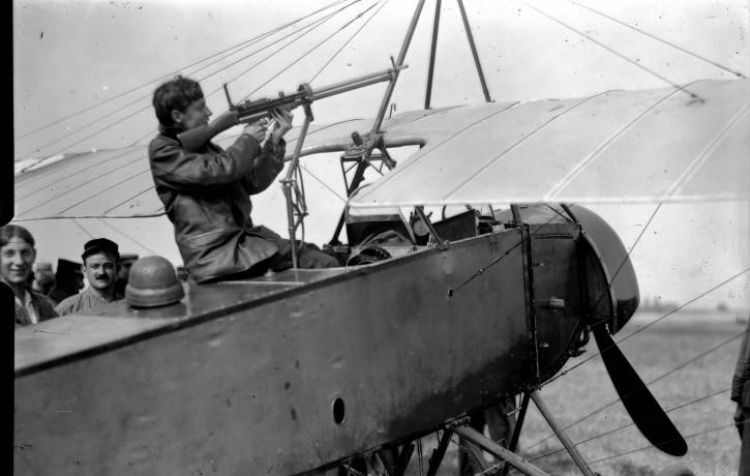 A pilot sitting on a French Morane-Saulnier L with a forward-firing gun, attempting to mount it to the plane