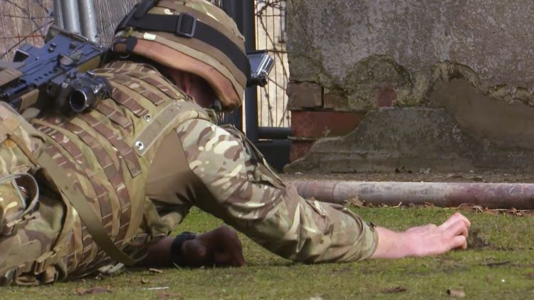 Soldier searching for booby trap on bomb disposal and search exercise