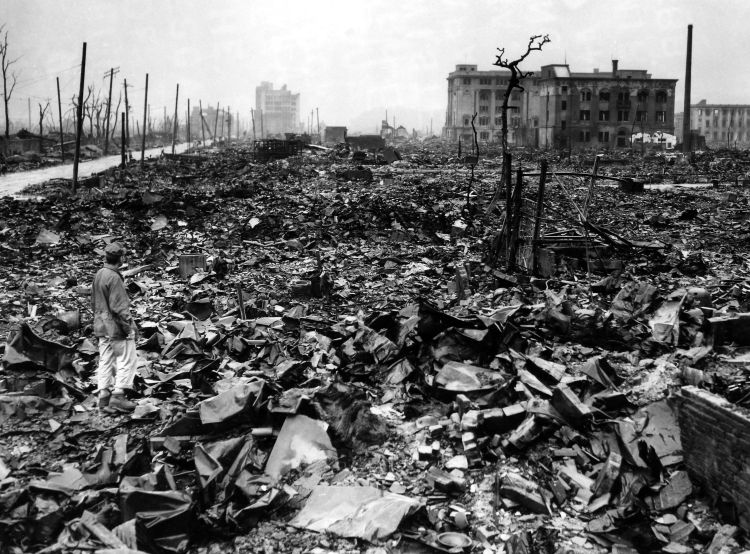 An unidentified newsman stands amid the rubble of Hiroshima a month after the atomic bomb was dropped on the city Credit: UPI/Press Association Images