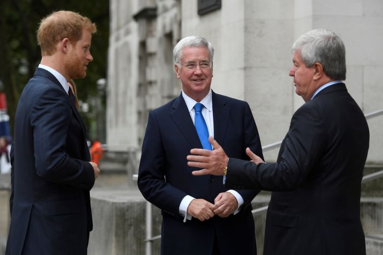 Prince Harry (left) is greeted by Defence Secretary, Michael Fallon and the Chair of the Royal Foundation, Keith Mills (right)