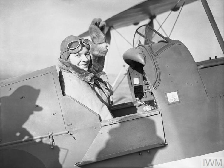 Pauline Gower, Commandant of the Air Transport Auxiliary Women's Section, waving from the cockpit of a de Havilland Tiger Moth at Hatfield, Hertfordshire, prior to a delivery flight, 10 January 1940. Credit © IWM (C 380)