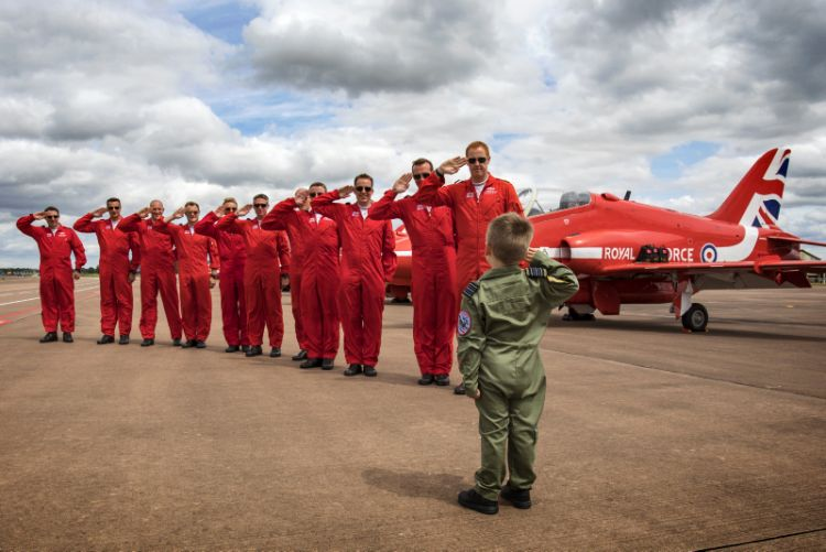 Jacob Newson (5yrs) takes a salute from his heroes the Red Arrows pilots, at the Royal International Air Tattoo at RAF Fairford.