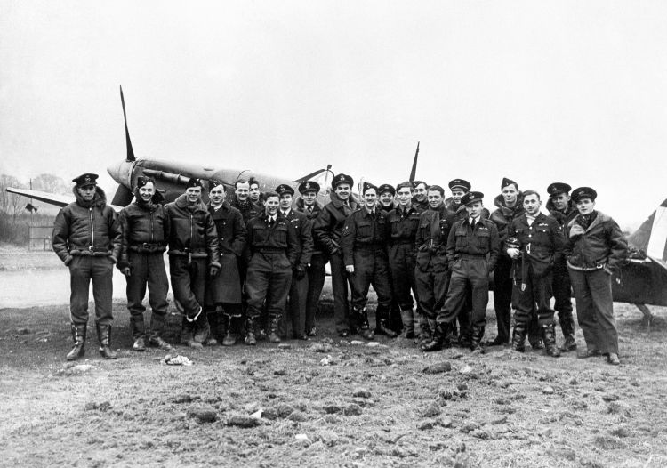 RAF personnel pose in front of a Spitfire - an aircraft that proved vital in protecting Britain's skies during World War Two (Picture: PA).