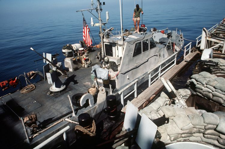 US Navy patrol boat tied up to US barge being used for combat operations. (Image: US Navy)