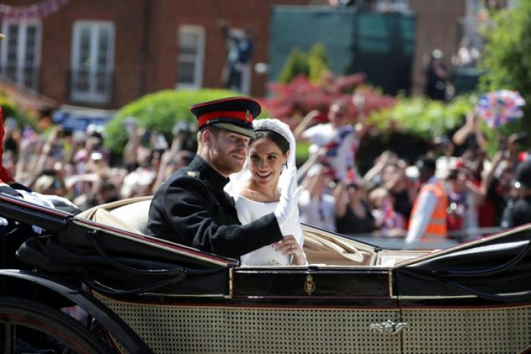 Prince Harry and Meghan waving in carriage procession on their wedding day