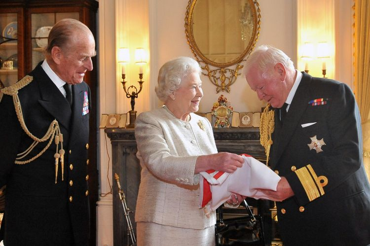 Prince Philip and the Queen presenting Sir Donald Gosling with a flag at Windsor Castle during a ceremony making him Vice Admiral of the UK