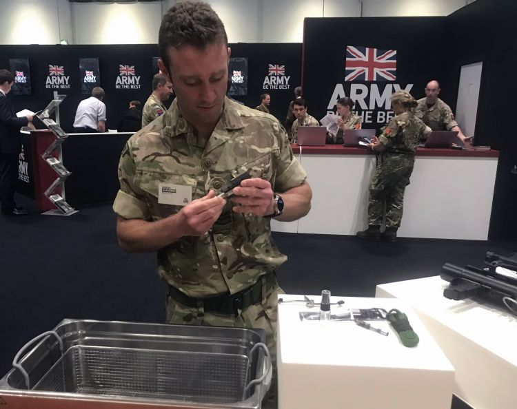 Sgt Dan Birks displays the Ultrasonic Cleaning Bath at DSEI fair. Credit: Georgina Coupe, BFBS