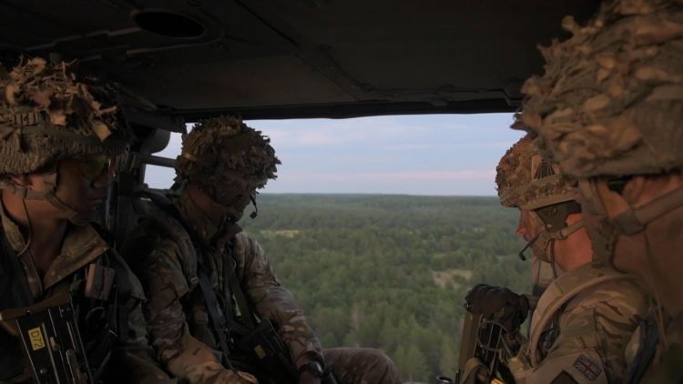 Soldiers look over Camp Grayling from a Chinook before dropping