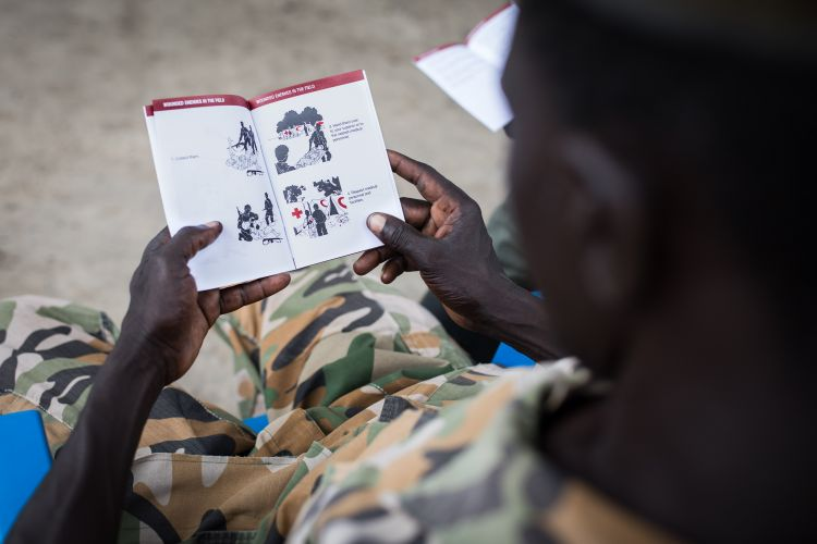 South Sudanese soldier looking at a first aid text book DATE UNKNOWN CREDIT ICRC FlorianSeriex